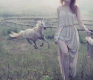 Empfindlicher Brunette, der mit Pferd im Hintergrund aufwirft lizenzfreie stockbilder