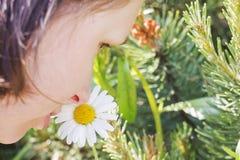 Empfindlicher Duft und Naturschönheit Eine Frau mit einem romantischen Gesicht schnüffelt eine weiße Blume lizenzfreie stockfotos