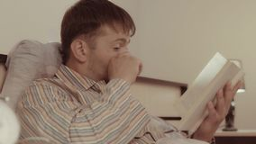 Empfindlicher junger Mann, der eine rührende Geschichte in seinem Buch liest stock video