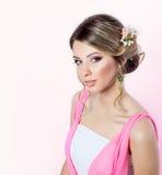 Empfindliches Bild eines Schönheitsmädchens wie eine Braut mit heller Make-upfrisur mit Blumenrosen im Kopf in einem rosa Kleid Stockbild