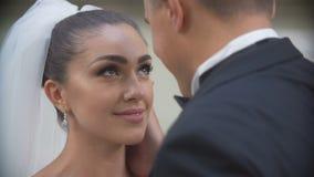 Empfindliches Porträt des Bräutigams, der zart seine schöne lächelnde Braut im Kopf küsst Ansicht über seine Schulter Nahaufnahme stock video