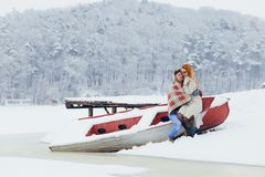 Empfindliches Porträt des reizenden glücklichen Paars, das auf dem Boot sitzt Die schöne rote Hauptfrau sitzt auf den Schößen Lizenzfreies Stockfoto