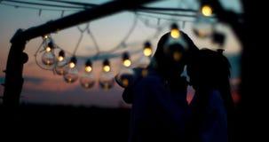 Empfindliches Porträt von zwei Paare cilhouettes, die hinter der Lichterkette während des Sonnenuntergangs stehen Der Kerl ist za stock video footage