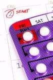 Empfängnisverhütende Pille auf dem Kalender Lizenzfreie Stockfotos