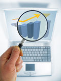Emphasis on Success!. A man's hand holds a magnifying glass to emphasize a rising trend on a chart showing on a laptop computer monitor Royalty Free Stock Photo