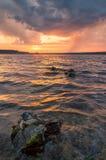 Empiedra la tormenta del lago en la puesta del sol Fotografía de archivo