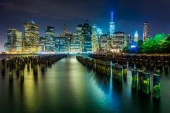 Empilages de pilier et l'horizon de Manhattan la nuit, vu du ruisseau Photo stock