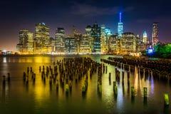 Empilages de pilier et l'horizon de Manhattan la nuit, vu du ruisseau Photo libre de droits