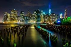 Empilages de pilier et l'horizon de Manhattan la nuit, vu du ruisseau Photos stock