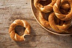 Empilez le bagel turc Simit dans un plat et le bagel mordu sur le fond en bois images stock