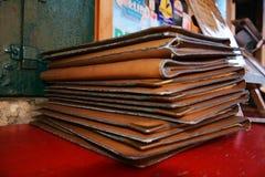 Empilez le fond en cuir brun de menu sur la table photo libre de droits