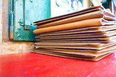 Empilez le fond en cuir brun de menu sur la table rouge, fermez-vous  image libre de droits