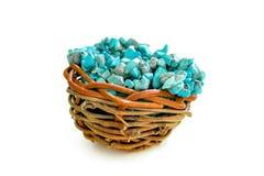Empilez les pierres de la turquoise crue dans le petit nid en bois sur un fond blanc Photographie stock libre de droits