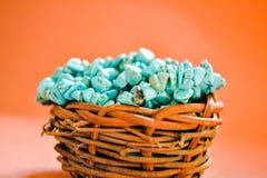 Empilez les pierres de la turquoise crue dans le petit nid en bois sur un fond brun Photos stock