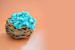 Empilez les pierres de la turquoise crue dans le petit nid en bois sur un fond brun Image stock