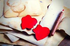 Empilez les vieux papiers, le carnet, le crayon en bois et deux coeurs rouges de vintage sur la toile de jute, fond de toile à sa Photo libre de droits