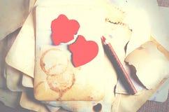 Empilez les vieux papiers, le carnet, le crayon en bois et deux coeurs rouges de vintage sur la toile de jute, fond de toile à sa Image stock