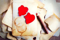 Empilez les vieux papiers, le carnet, le crayon en bois et deux coeurs rouges de vintage sur la toile de jute, fond de toile à sa Photographie stock