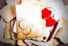 Empilez les vieux papiers, le carnet, le crayon en bois et deux coeurs rouges de vintage sur la toile de jute, fond de toile à sa Images stock