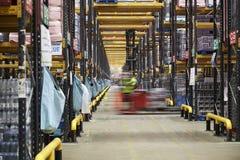 Empilhadeira que conduz através de um corredor em um armazém, borrão de movimento fotos de stock royalty free