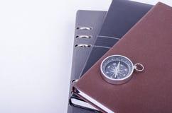 Empilhando diários e compasso no fundo branco Imagens de Stock