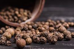 Empilhe grões orgânicas inteiras da pimenta preta na tabela de madeira com c foto de stock royalty free