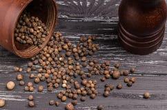 Empilhe grões orgânicas inteiras da pimenta preta na tabela de madeira com p imagem de stock royalty free