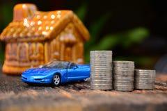Empilhe moedas ao lado do carro e da parte dianteira azuis da mini casa para o financia Imagens de Stock