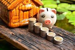 Empilhe moedas ao lado do mealheiro e da parte dianteira da mini casa para o financ Imagens de Stock