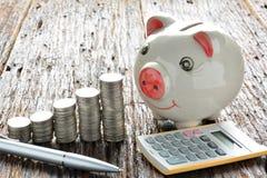 Empilhe moedas, calculadora e mealheiro na tabela de madeira Foto de Stock Royalty Free