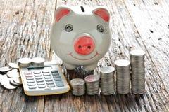 Empilhe moedas, calculadora e mealheiro na tabela de madeira Imagem de Stock