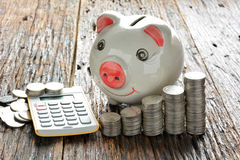Empilhe moedas, calculadora e mealheiro na tabela de madeira Foto de Stock