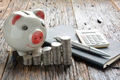 Empilhe moedas, calculadora e mealheiro na tabela de madeira Fotografia de Stock Royalty Free
