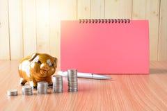 Empilhe moedas, calculadora e mealheiro na tabela e no sp de madeira da cópia Fotografia de Stock Royalty Free