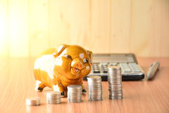 Empilhe moedas, calculadora e mealheiro na tabela e no sp de madeira da cópia Imagem de Stock Royalty Free