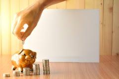 Empilhe moedas, calculadora e mealheiro na tabela e no sp de madeira da cópia Imagem de Stock