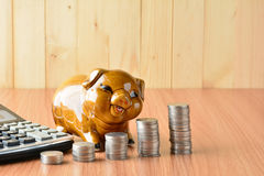 Empilhe moedas, calculadora e mealheiro na tabela e no sp de madeira da cópia Imagens de Stock Royalty Free