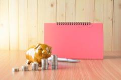 Empilhe moedas, calculadora e mealheiro na tabela e no sp de madeira da cópia Fotos de Stock Royalty Free