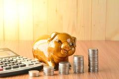 Empilhe moedas, calculadora e mealheiro na tabela e no sp de madeira da cópia Foto de Stock Royalty Free