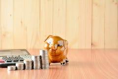 Empilhe moedas, calculadora e mealheiro na tabela e no sp de madeira da cópia Foto de Stock