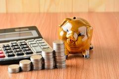 Empilhe moedas, calculadora e mealheiro na tabela e no sp de madeira da cópia Fotos de Stock