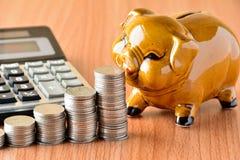 Empilhe moedas, calculadora e mealheiro na tabela e no sp de madeira da cópia Fotografia de Stock