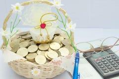 Empilhe moedas de ouro na cesta com pena e calculadora dos vidros Imagem de Stock Royalty Free