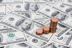 Empilhe moedas de um centavo dos E.U. em um gráfico de barra de ascensão no fundo com notas de dólar do americano cem do dinheiro Fotos de Stock Royalty Free