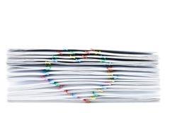 Empilhe o documento da sobrecarga com o clipe coração-dado forma colorido no fundo branco Fotografia de Stock