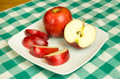 Empire apple slices on white plate Stock Photography