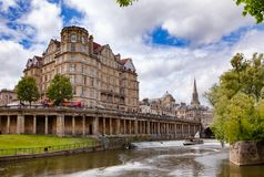 Empire Hotel and the Pulteney weir on River Avon at Bath Somerse. BATH, UK - JUN 11, 2013: View of The Empire Hotel near Pulteney Bridge with the Colonnade under Royalty Free Stock Images
