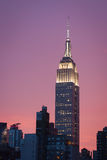Empire state building with bright purple sky at sunset - New York city. View of the top part of the Empire state building with bright purple sky at sunset - May Stock Photos