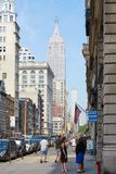 Empire State Building and Fifth Avenue sidewalk with people in New York Stock Images