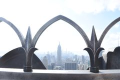 Empire State Building Framed by Gothic railing. Empire State building framed by railing. Sunny day on New York rooftop Royalty Free Stock Photography